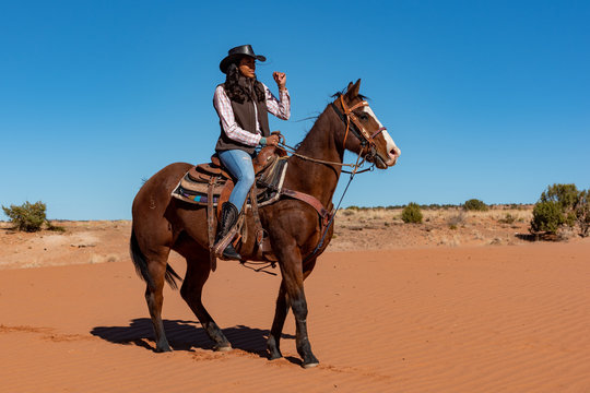 young native american woman riding horse in the desert