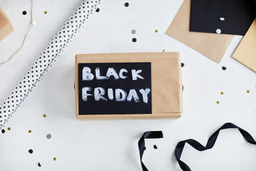 Top view of wrapped gift box with painted lettering Black Friday lying on white table covered with confetti