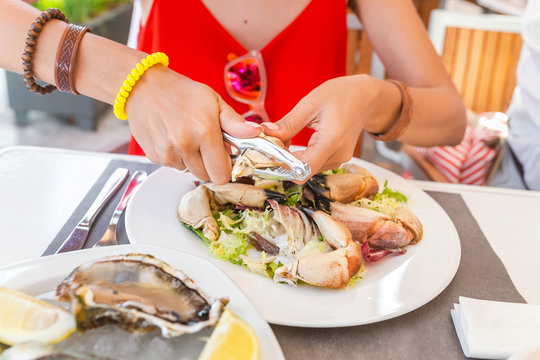 Woman eating crab claw using special pliers tool to reach for delicious white meat. Spanish mediterranean seafood cuisine concept