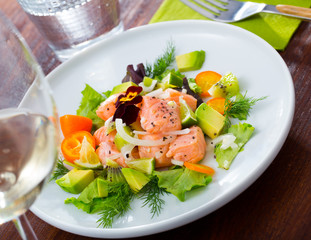 Ceviche from salmon on plate with cumquat, green dill  and avocado