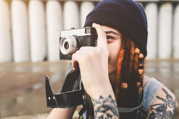 young girl with tattoos and dreadlocks in a blue hat photographs a vintage camera on the background of a concrete wall