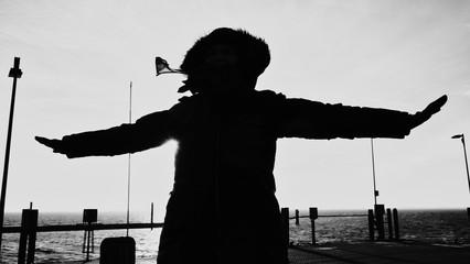 Frau im Gegenlicht lehnt sich gegen den starken Gegenwind. Winter auf der Nordseeinsel Baltrum