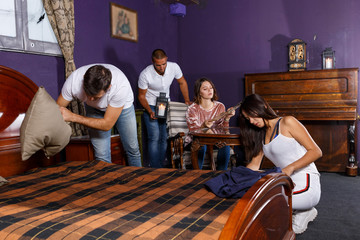 Young adults in escape room with antique furnitures