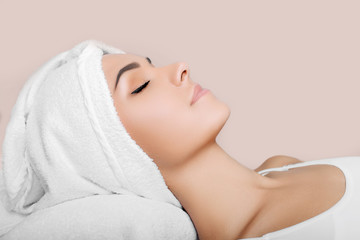 woman with clean fresh face, with towel on head, relaxing after spa receiving treatment. Women with perfect skin enjoying a skin care treatment