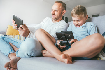 Father and preteen son playing together PC games on electronic devices