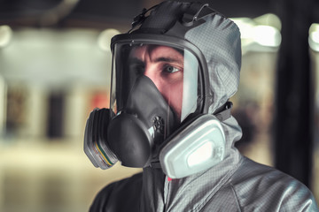 The worker of shop of coloring in overalls and a protective mask