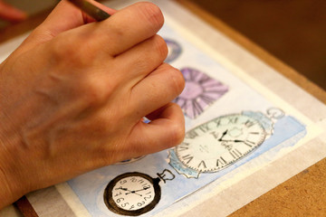 A hand of girl draws a sketch depicting many different clocks