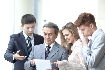 businessman and his team look at the screen of the digital tablet