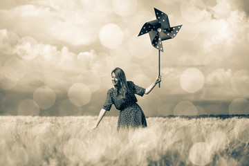 a young girl is standing on a wheat field with pinwheel and waiting for rain. Image in old sepia...