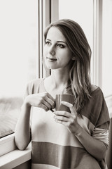 Beautiful young woman with cup near window at home. Image in black and white color style