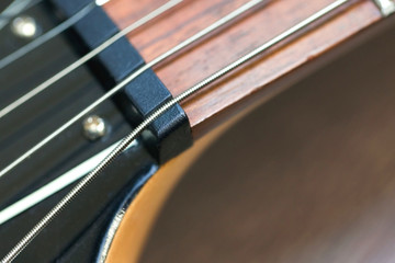 guitar  with wooden brown neck and strings, close up blurry background, texture, abstract