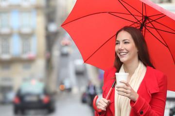 Happy woman walking with a takeaway drink in winter