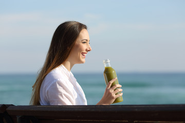 Side view of a woman holding a vegetable juice