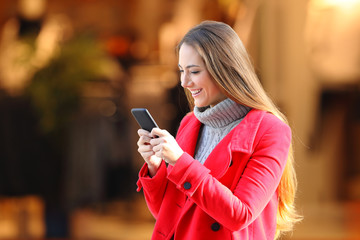 Woman using a smart phone in winter in a commercial centre