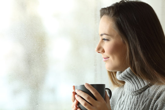 Happy woman looking to rain holding coffee through the window