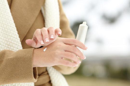 Woman hand hydrating skin applying cream in winter