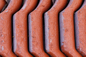 Background of roof tiles arranged on each other. The red hue of the roof tiles.