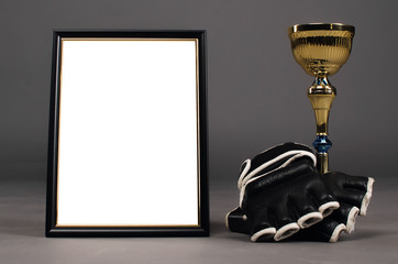Empty photo frame with copy space for fighting winner, boxing gloves and golden award cup isolated on gray studio background.