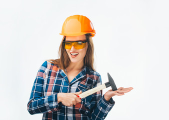 Young happy attractive girl in building orange helmet and glasses with hammer. Full isolated studio picture from emotional craftswoman.