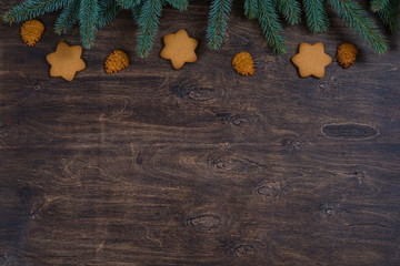Background with gingerbread Christmas cookies and fir-tree branches