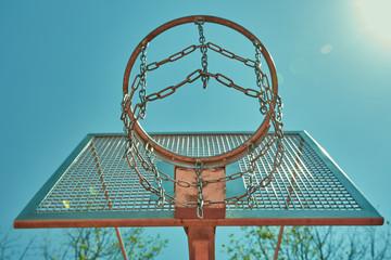 Basketball hoop on basketball court under blue sky