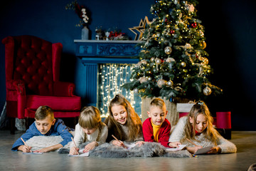 a group of young children lie on a warm woolen blanket on the background of a Christmas tree and write a letter to Santa