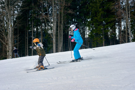 Young boy with mother enjoying ski vacation at mountains