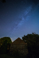 Milky way over old brick and stone building