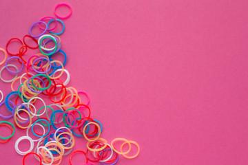 Rainbow loom bands bracelets on pink background. Colorful ties for waving hair. Children hobby - handmade bracelets.