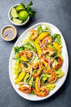 Fresh Shrimps, Mango Avocado lettuce salad, olive oil and lemon dressing. healthy food. Top view, gray background