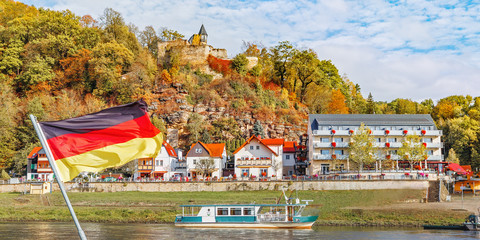 Wall Mural - Resort Rathen in Saxony, Germany. View over river Elbe. Waving National Flag of Germany, in backdrop - in National Park Saxony Switzerland. Popular travel destination in Saxony, UNESCO heritage.