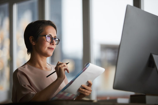 Confident businesswoman with document looking at computer screen and making working notes in office