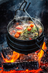 Tasty and homemade hunter's stew on campfire