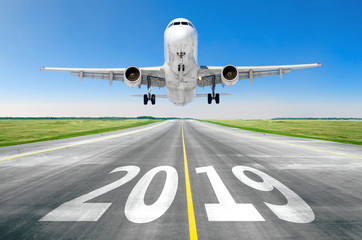 The inscription on the runway 2019 surface of the airport runway texture with take off airplane. Concept of travel in the new year, holidays.