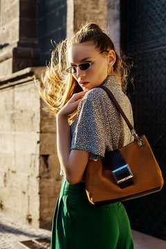 Outdoor fashion portrait of young beautiful fashionable woman walking street, model wearing sunglasses, leopard print shirt, green trousers, holding brown suede bag