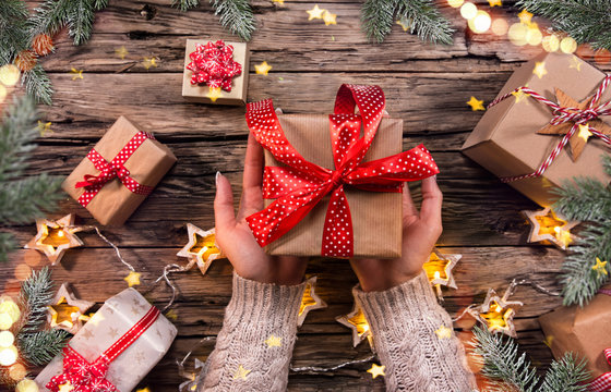 Top view of woman hands with gift box.