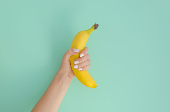 Female hand holding a banana on a mint background. Minimal fruit concept.