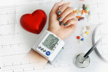 Monitoring of blood pressure of hypertensive patient, with red heart, stethoscope and pills on electrocardiogram