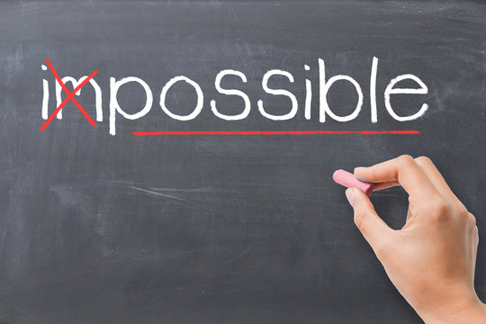 Change impossible into possible concept, with woman handwriting with chalk on blackboard