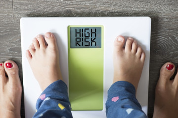 Childhood obesity high risk for health problems with child's feet on weight scale  under the supervision of his mother