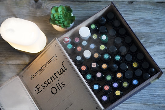 Aromatherapy concept with essential oils and oil diffuser on wooden background