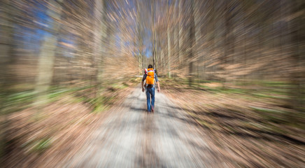 Traveler hiking through deep forest in the mountains - blurred motion techique used to convey fast paced movement
