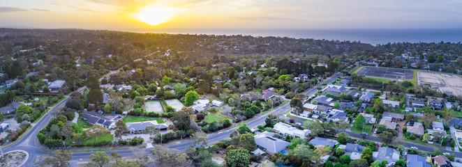 Sunset over houses on ocean coastline - aerial panorama