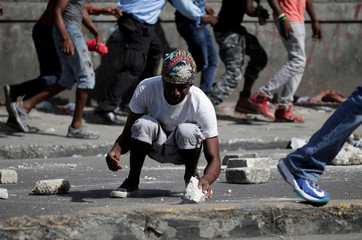 A protester breaks a rock during clashes with neighbours during a march to demand an investigation into what they say is the alleged misuse of Venezuela-sponsored PetroCaribe funds, in Port-au-Prince