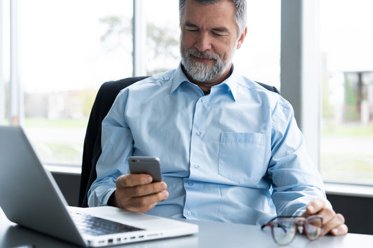 Mature business man in formal clothing using mobile phone. Serious businessman using smartphone at work. Manager in suit using cellphone in a modern office.