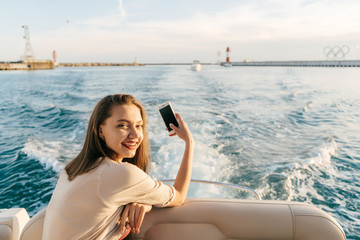 smiling long-haired girl floating on the blue sea, taking pictures of the landscape
