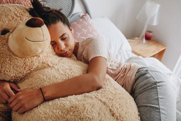 Girl sleeping on bed holding a teddy bear