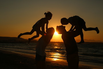 Silhouettes of young parents holding their children at sunset - Stock image