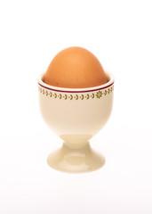Porcelain egg cup with brown egg inside.