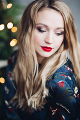 Portrait of gorgeous woman with perfect make up, red lips and smooth skin. Charming blonde looking at camera and smiling. Cheerful facial expressin of pretty model.